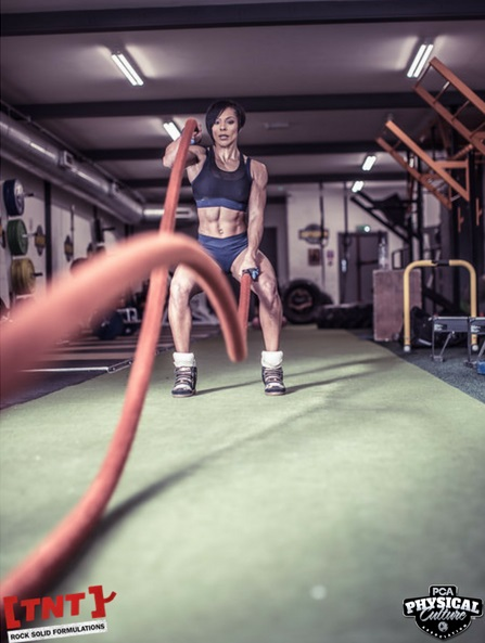 Shereen Henrick performing a double handed wave with battle ropes for high intensity interval training.
